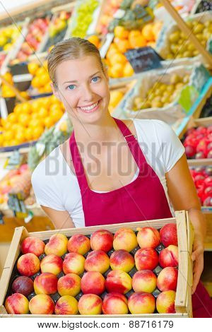 Woman holding a crate of fruit