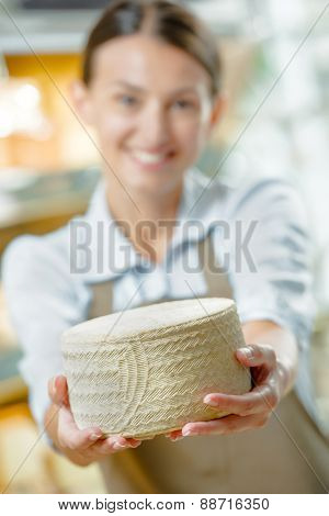 Woman holding a wheel of cheese