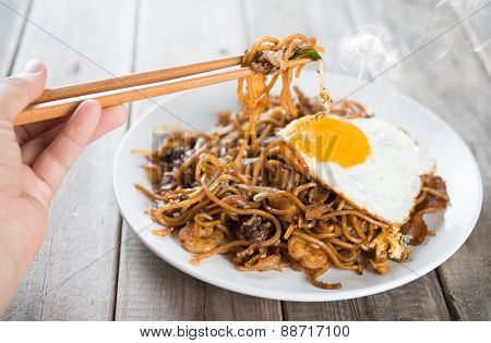 Close-up human hand holding chopsticks eating stir fried char kuey teow with over wooden background.