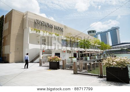 SINGAPORE - FEBRUARY 18, 2015:  Customs House on the waterfront Marina Bay in Singapore. In the background is the famous Marina Bay Sands.
