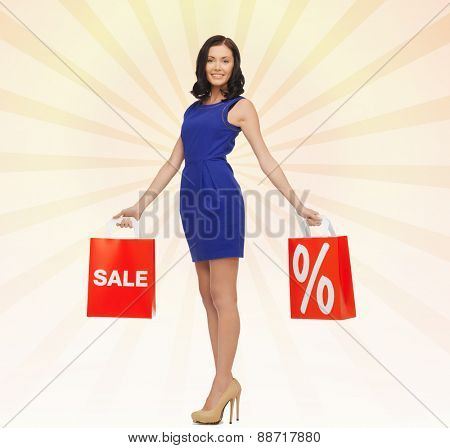 people, retail, sale, discount and consumerism concept - happy young woman in dress with red shopping bags over beige burst rays background