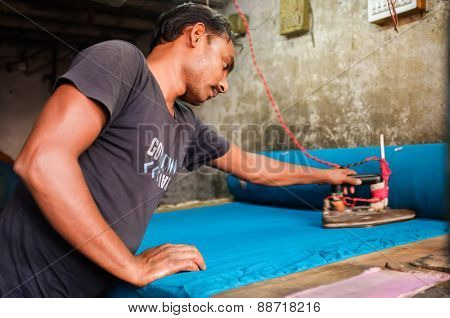 MUMBAI, INDIA - 08 JANUARY 2015: Man ironing with an electric iron indoors in Dhobi ghat.
