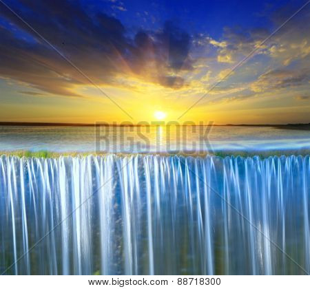 Scene with waterfall on sunset sky background