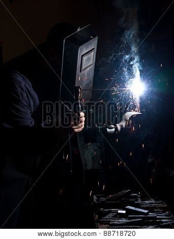 Man welding - only light is from electrical flux