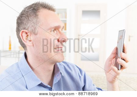 Smiling Deaf man talking using mobile phone at home