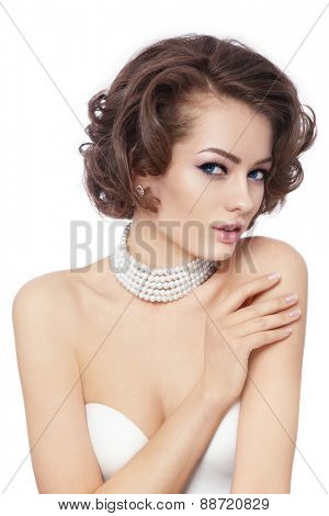 Young beautiful sexy woman with stylish curly hairdo and pearl necklace over white background