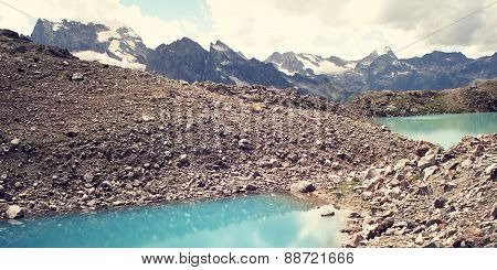 Bright Blue Water In The Alpine Lake - Retro Filter Photo.