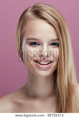 young pretty blonde woman with hairstyle close up and makeup on pink background smiling