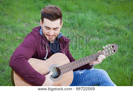 Cool handsome guy with beard playing guitar at outside