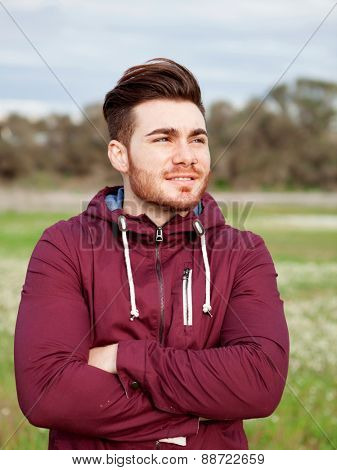 Casual cool young man with beard in the field