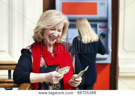 Mature blonde woman counting money near automated teller machine in shop