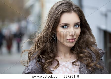 Portrait close up of young beautiful brunette woman, on spring street background