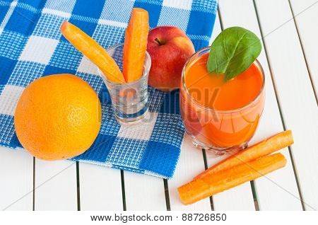 Healthy homemade carrot juice in glass and fresh carrot, apple, orange, spinach on light wooden back