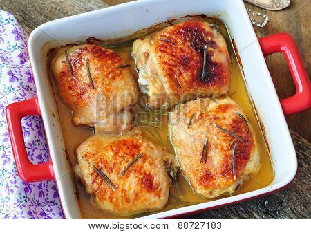 Roasted chicken thighs on a wooden table.image is tinted