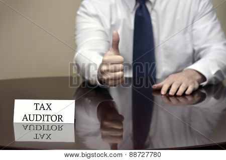 IRS tax auditor business card sitting at desk with hand showing thumbs up sign for audit success