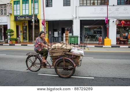 Old woman in bare feet transports folded cardboard boxes with an old bicycle
