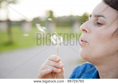 A Woman Blowing A Dandelion