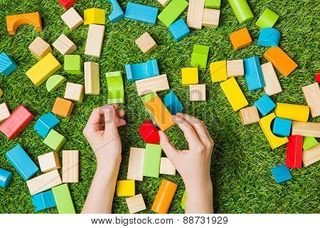 Hands constructing from color wooden blocks