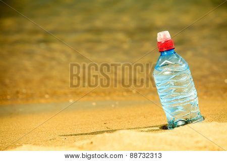 Bevarage. Bottle Of Water Drink On A Sandy Beach.