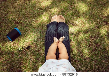 Little Baby Toddler Sitting On Mom Knees In Park
