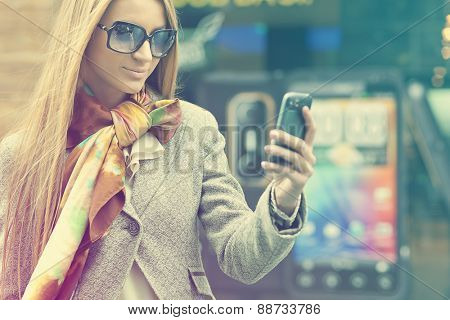 Young Woman with mobile phone walking background is blured city
