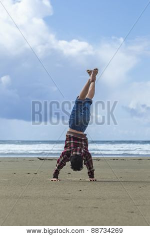 Boy does handstand on the beach.