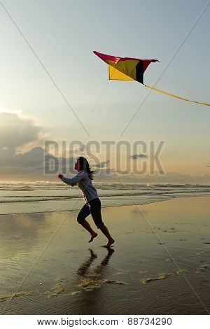 Woman with kite at beach.