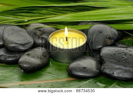 Candle and black stones on wet banana leaf