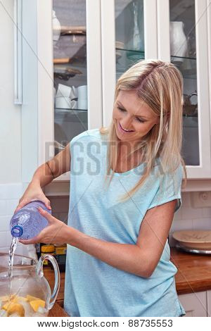 young women pouring water into jug of ice and lemon in the kitchen at home