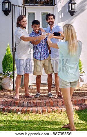 women taking photo pictures of group friends on mobile cellphone camera outdoors at garden party