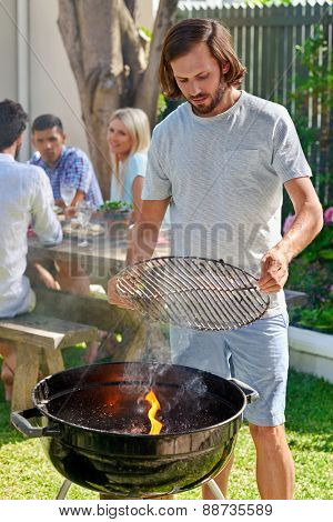 young man preparing to grill on fire for friends outdoor barbecue garden party