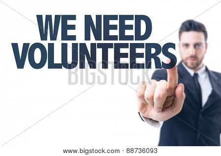 Business man pointing the text: We Need Volunteers