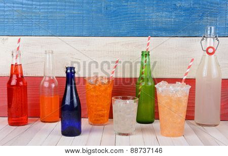 Assorted drink bottles and glasses full of soda on a rustic whitewashed table with a red, white and blue background.