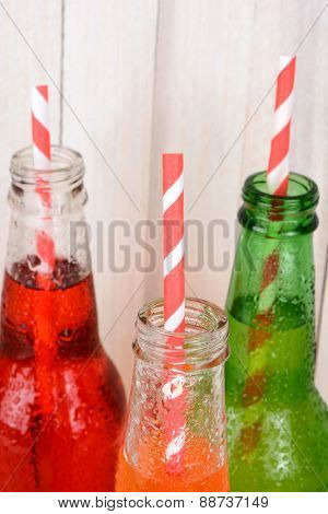 Closeup of soda bottle necks with straws.