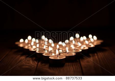 Candles in the shape of heart on old wooden background