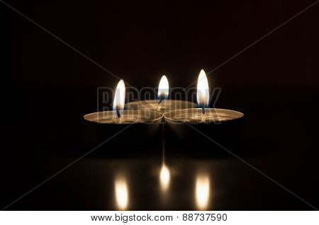 Three candles on a dark background reflected from the surface