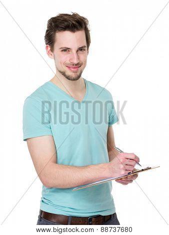 Caucasian man writes on clipboard