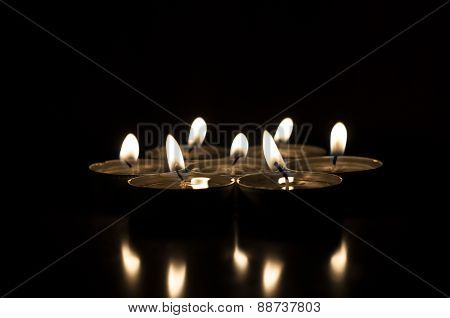 Several candles on a dark background reflected from the surface