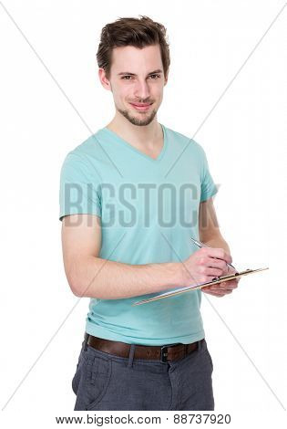 Caucasian man takes notes on clipboard