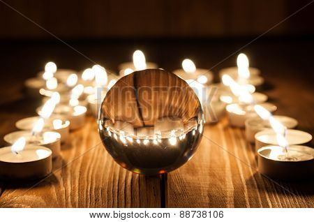 Glass transparent ball and burning candles on old wooden background
