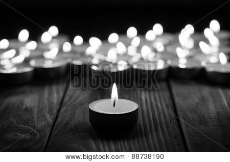 One candle and Candles on old wooden background