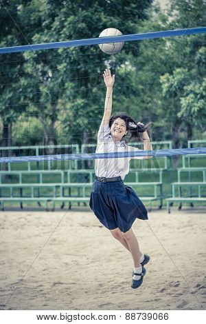 Cute Thai Schoolgirl Is Playing Beach Volleyball In School Uniform In Vintage Color. Focus On The Mo
