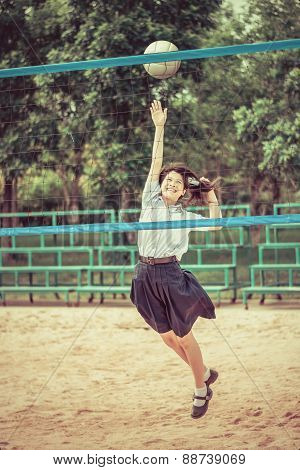 Cute Thai Schoolgirl Is Playing Beach Volleyball In School Uniform In Retro Color. Focus On The Mode