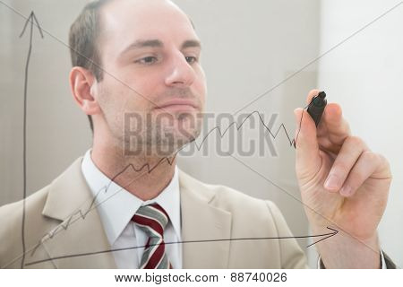 Businessman Drawing A Graph On A Glass Panel