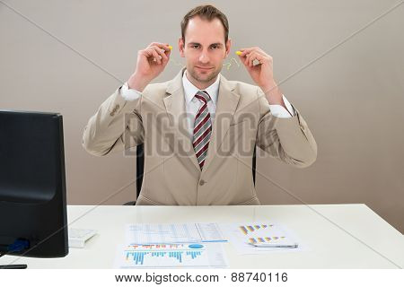 Businessman Inserting Earplug In Ears