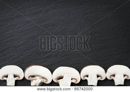 Several sliced mushrooms isolated on dark grey slate stone copyspace.