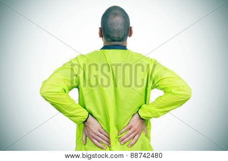 a young caucasian sportsman wearing sport clothes with his hands in his back because of his low back pain