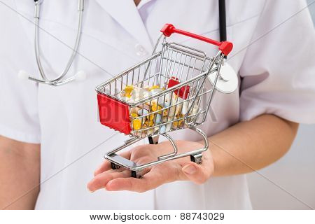 Doctor Holding Shopping Cart With Pills