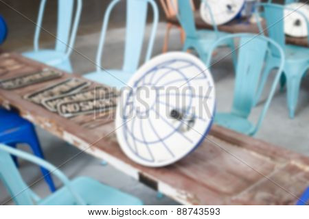 Blurry Defocused Image Of Blue Metal Chair With Old Wooden Door Panel For Background