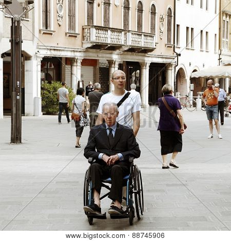 Venice, Mestre-june 29, 2014: Young Man Pushing A Senior Man In A Wheelchair On Piazza Erminio Ferre